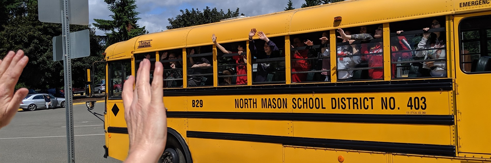 Staff waving at buses on last day of school.