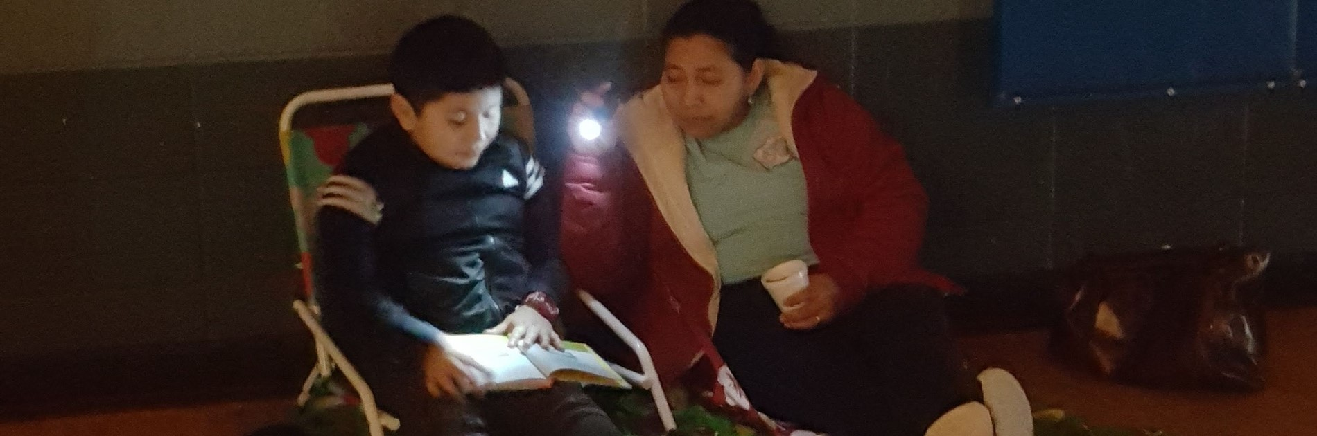 Student and parent reading by flashlight