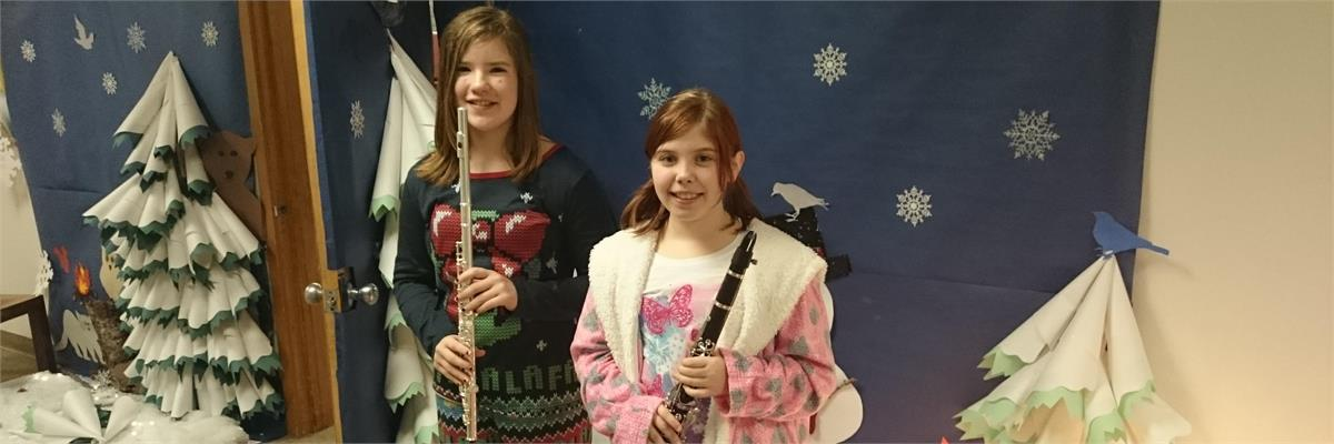 Two middle school students at the winter holiday music program - a flute and clarinet player