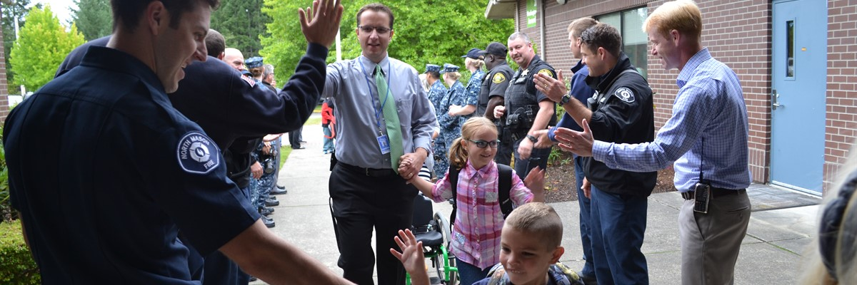 Students receive high fives as they enter Sand Hill on their first day.