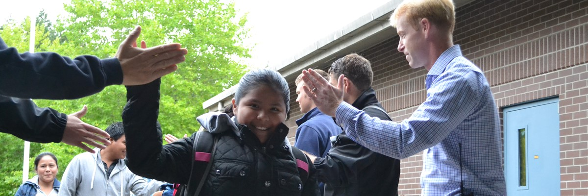 Sand Hill students get high fives from teachers and staff as they enter the school on their first day.