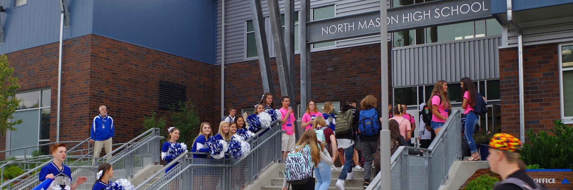 NMHS welcomes back students and staff as they enter the front of the school.
