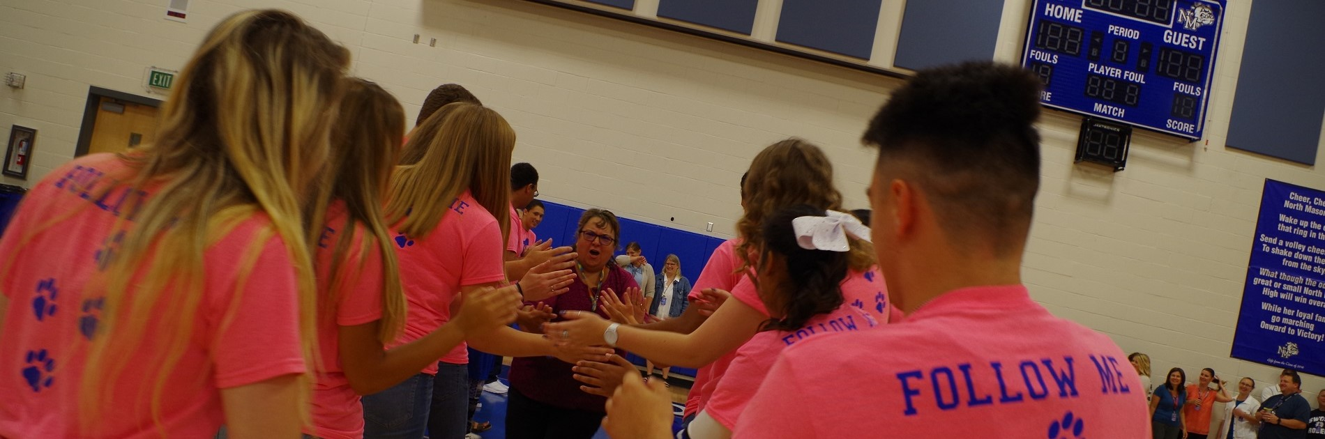 NMHS teacher high fives students at first assembly of the year.