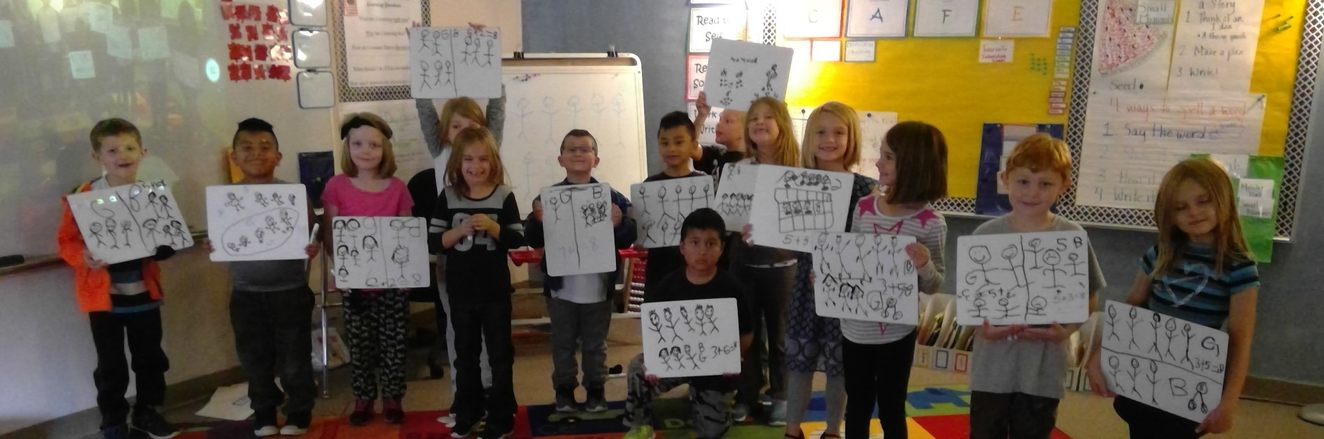 classroom of students holding drawings of stick figures